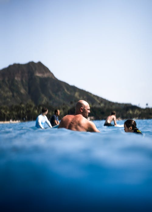 Man swimming in sea with other people on blurred background of mountain under cloudless sky