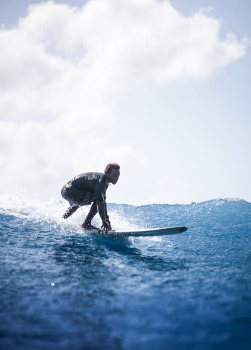 Side view of man in wetsuit riding on surfing board in wavy ocean