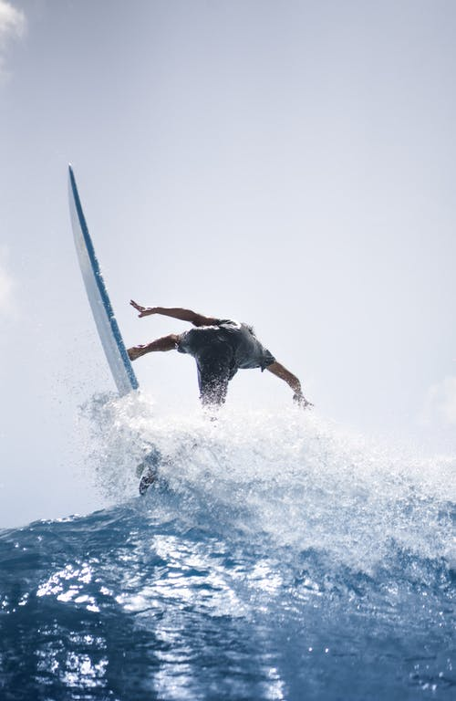 Anonymous person surfing on board in sea