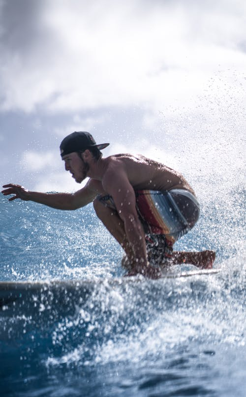 Back view of concentrated shirtless male surfer in shorts surfing in ocean against cloudy sky
