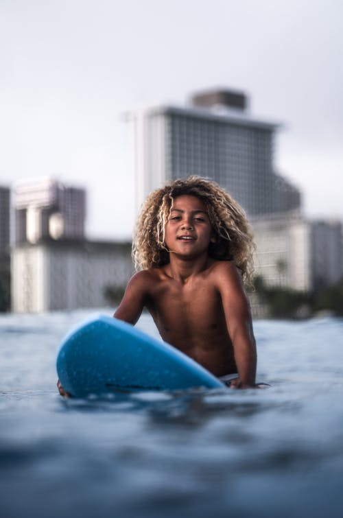 Fair haired boy sitting on surfboard in sea water and looking at camera on blurred background of cityscape
