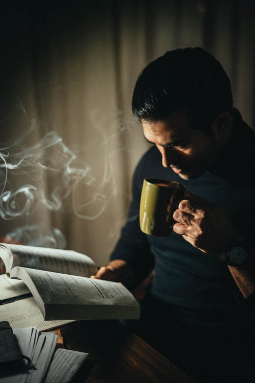 From above side view of concentrated male drinking hot beverage and reading book while sitting at table during paperwork in dark room with smoke