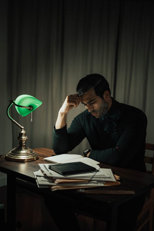 Thoughtful man doing paperwork at table in dark room