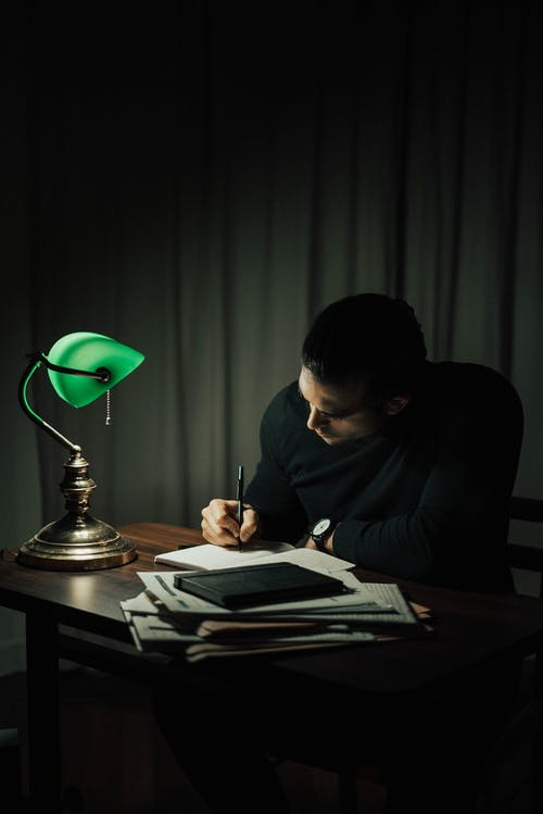 Concentrated male taking notes in notepad while sitting at desktop with documents in dark room with table lamp during paperwork at home