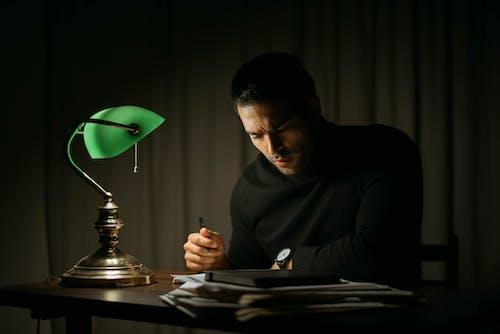 Smart man doing paperwork in dark room
