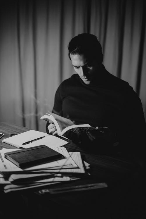 Black and white concentrated handsome male in dark turtleneck reading diary attentively while sitting at desk with papers in home office