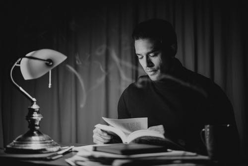 Black and white focused good looking male in casual wear reading book while sitting at desk with papers and bankers lamp in home office