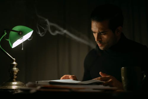 Pondering young male in black sweater reading book while sitting at desk with papers and green bankers lamp in dark home office