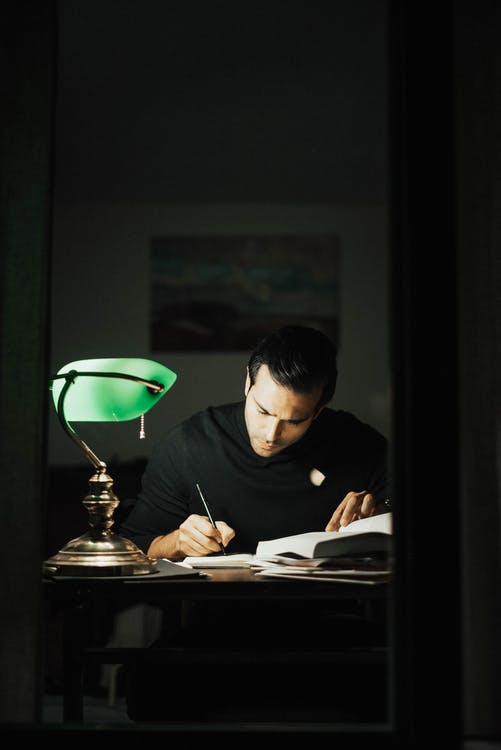 Concentrated young male wearing black turtleneck taking notes and reading books while sitting at desk with papers and bankers lamp in dark home office