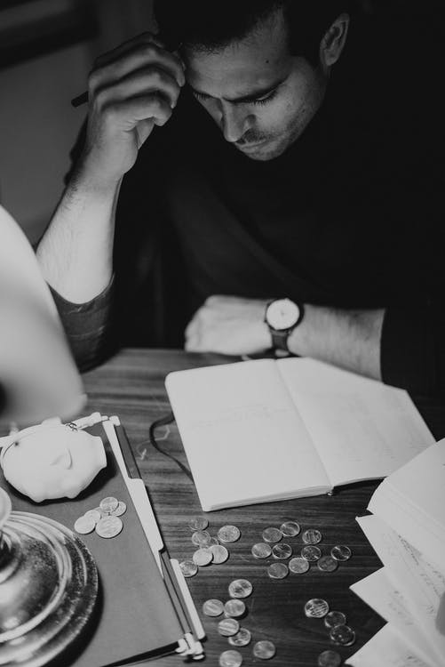 Crop pondering man analyzing expenses and taking notes