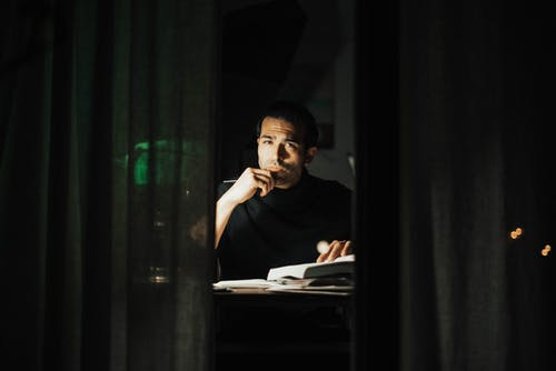 Serious young male wearing black turtleneck reading book and looking at camera while touching chin in contemplation and sitting at desk in dark home office