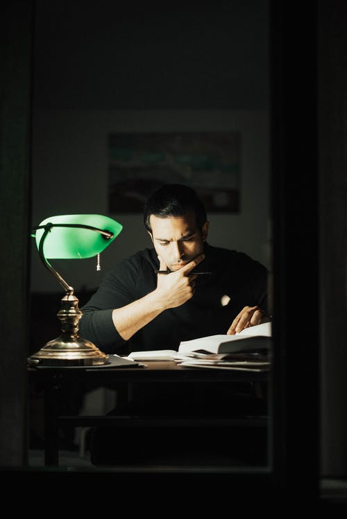 Serious brunet wearing black sweater reading book and doing paperwork while sitting at desk with papers and green bankers lamp in home office