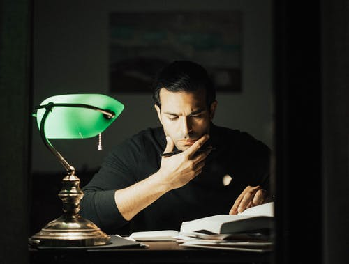 Serious young male wearing black turtleneck reading book and touching chin thoughtfully while studying in dark home office
