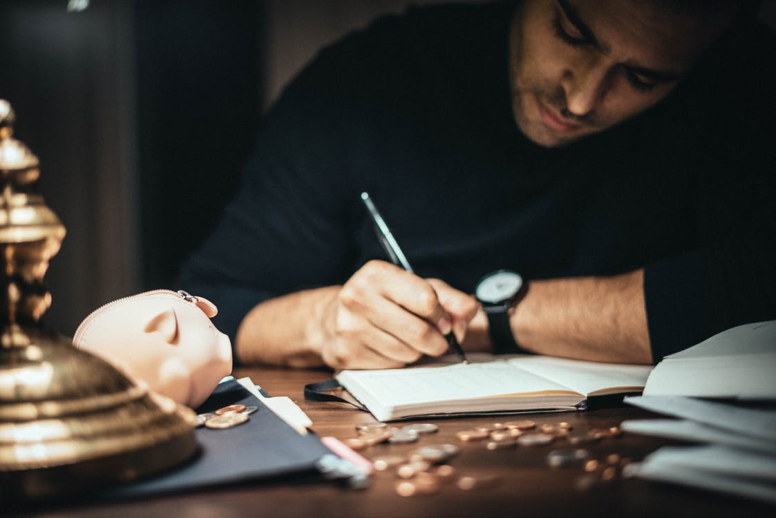 Crop elegant man taking notes in journal while working at desk with coins and piggybank in lamplight