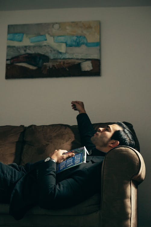 Side view of masculine handsome male in black suit lying on sofa with book and looking up