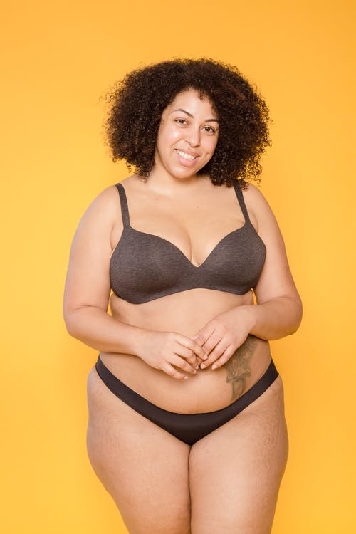 Smiling plump ethnic model in lingerie with tattoo