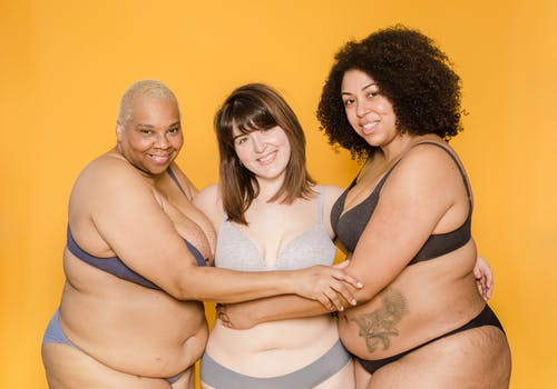 Cheerful plus size multiracial girlfriends in lingerie on yellow background