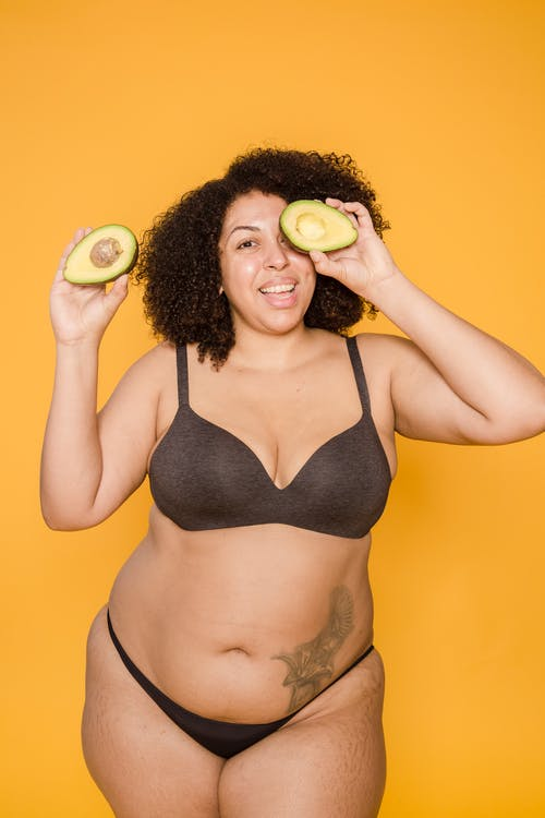 Smiling overweight ethnic model in lingerie with avocado halves