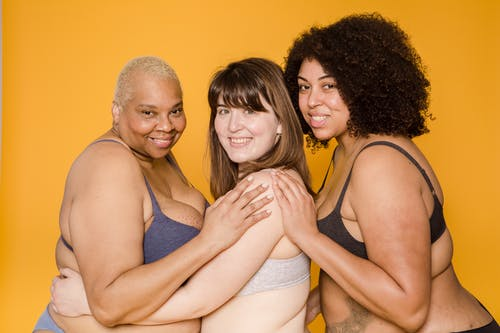 Happy plump multiracial models in lingerie on yellow background