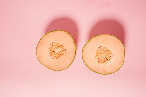Top view of ripe orange melon cut into halves for healthy diet placed on pink background in modern light studio