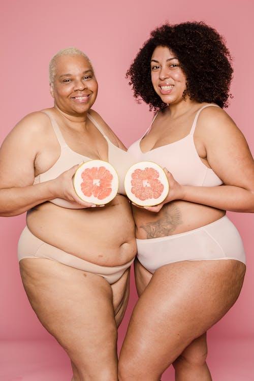 Woman in White Bikini Holding Two Doughnuts