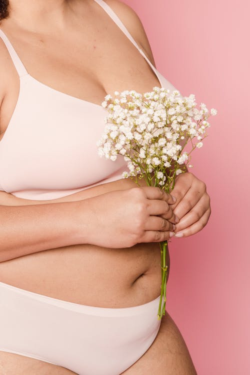 Crop overweight woman in lingerie with flowers