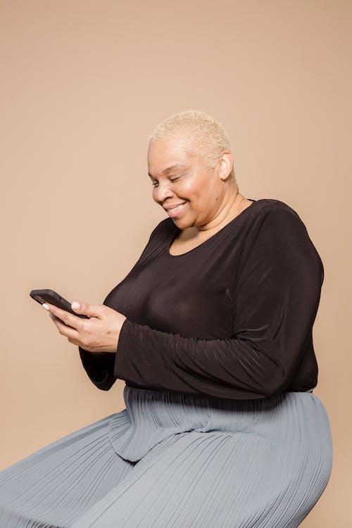 Smiling plump black woman browsing smartphone