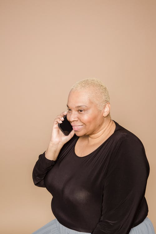 Side view of positive overweight African American female having phone conversation while sitting on beige background in modern light studio