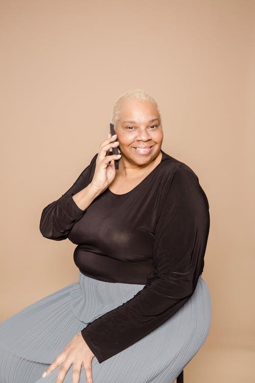 Smiling plump black woman having phone call