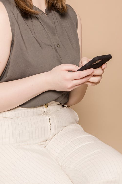 Unrecognizable plump female in stylish outfit text messaging on contemporary cellphone while sitting on beige background in modern light studio