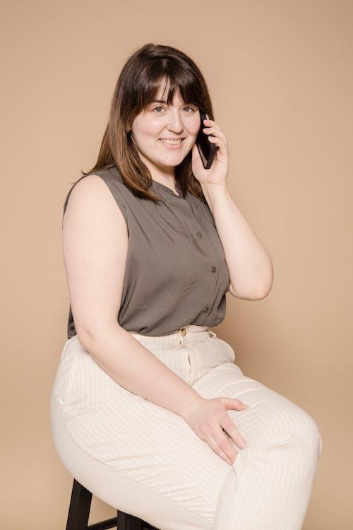 Cheerful plump Asian woman talking on phone