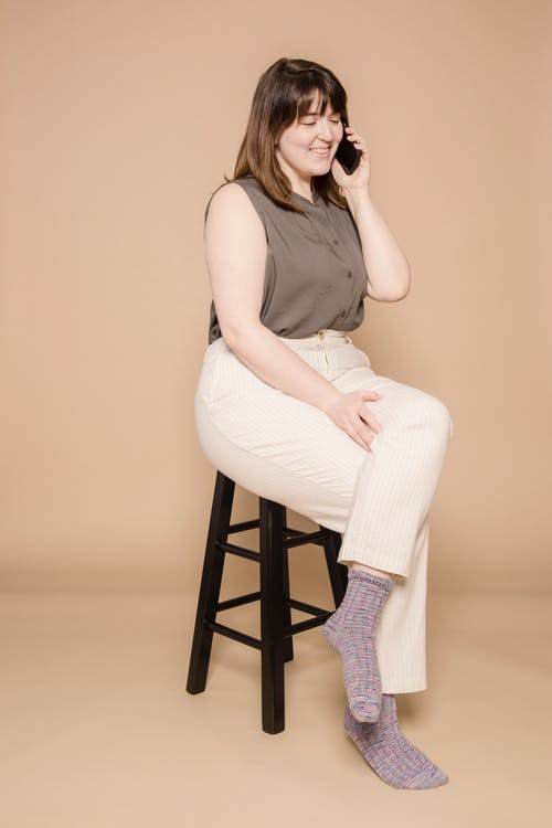 Full body of positive overweight Asian female having phone call while sitting on chair against beige background in light studio