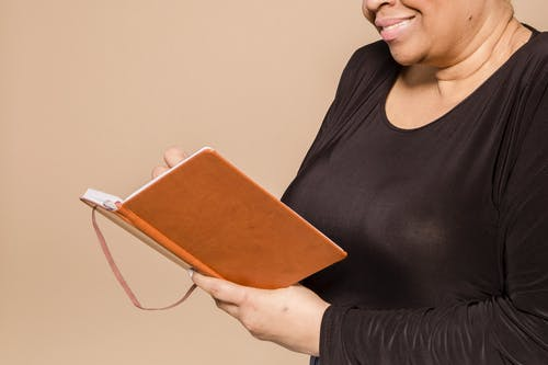 Crop cheerful black woman with notebook