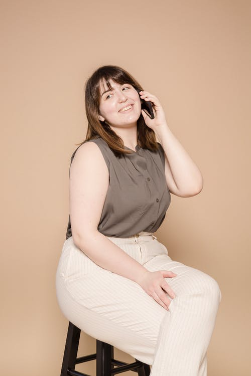 Content overweight Asian female wearing stylish outfit looking away and talking on smartphone while sitting on chair against beige background