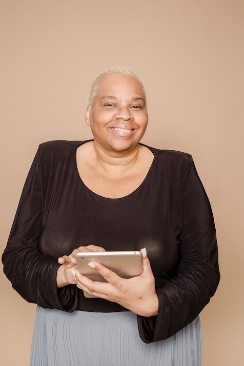 Joyful overweight black woman using tablet
