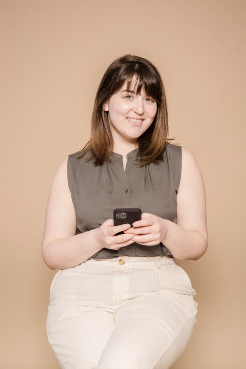 Content plump Asian female in stylish outfit text messaging on cellphone and looking at camera while sitting on beige background