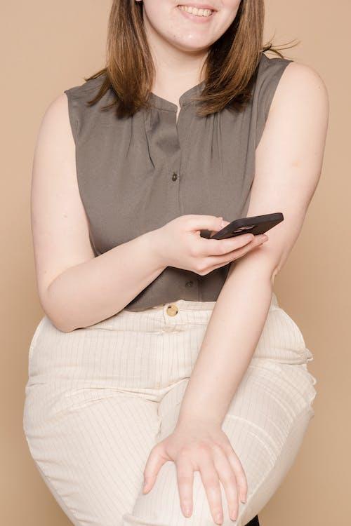 Crop cheerful woman using smartphone in studio