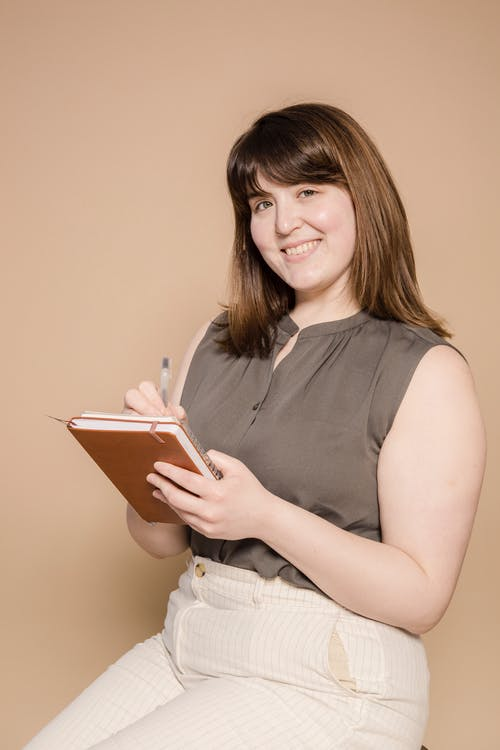 Cheerful Asian woman with notebook