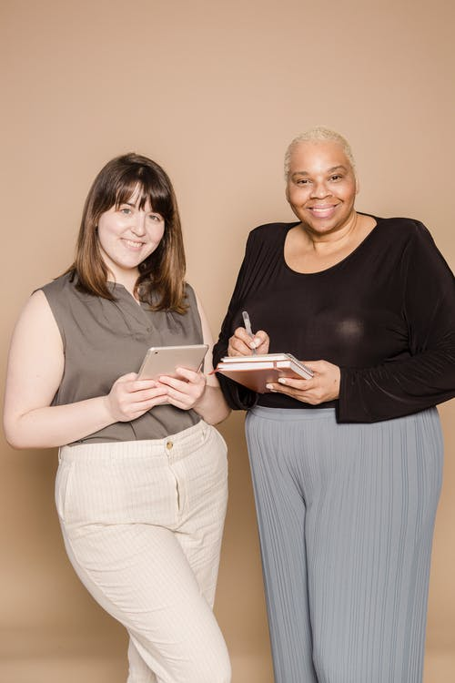 Happy Asian woman browsing tablet near overweight African American female colleague taking notes in notepad while looking at camera on beige background