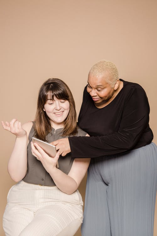 Happy overweight diverse women browsing tablet