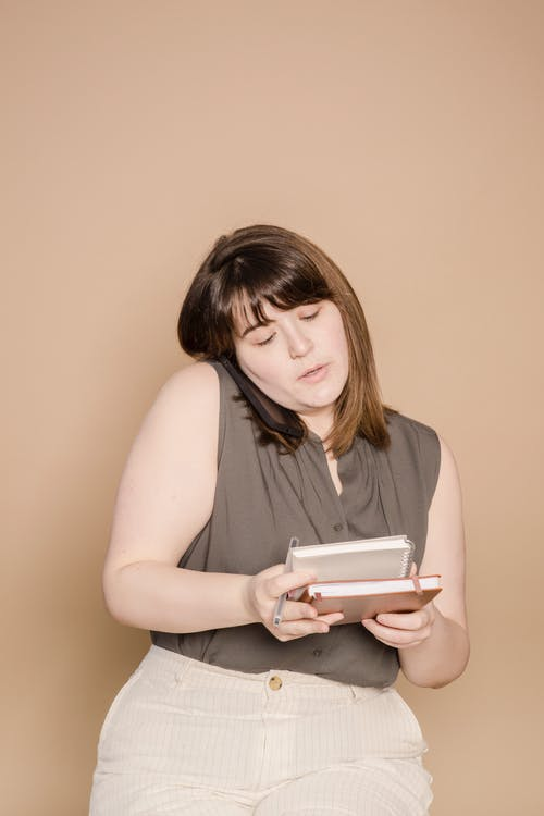 Focused plump Asian female worker speaking on cellphone while standing on beige background with notepads in hands during work in studio
