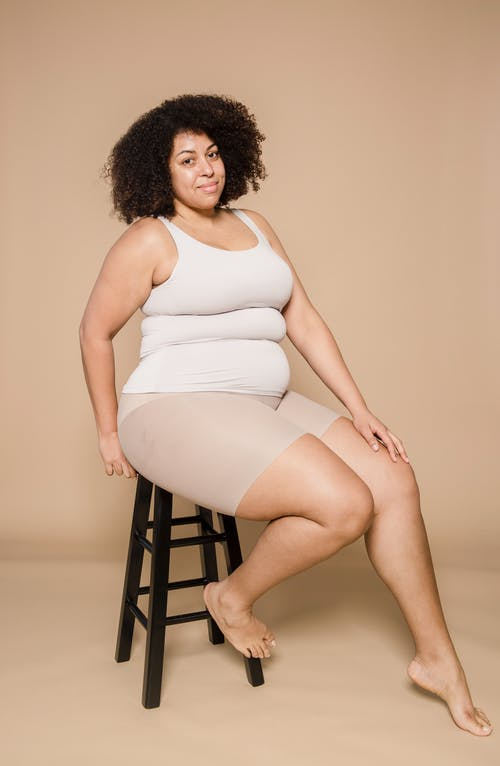 Content overweight black woman on chair