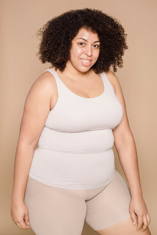 Delighted plump African American female with black hair wearing shorts smiling and looking at camera on beige background in studio