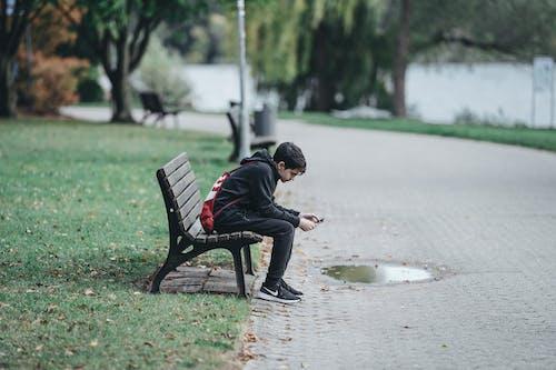 Teenage boy using smartphone on park bench
