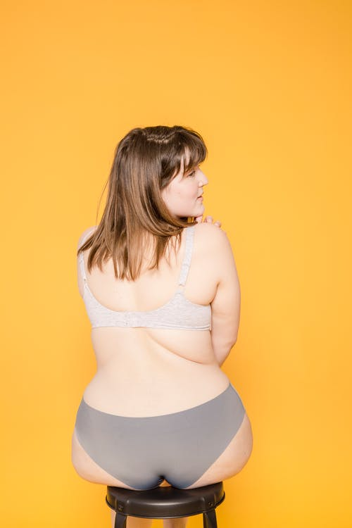 Overweight model in lingerie on yellow background