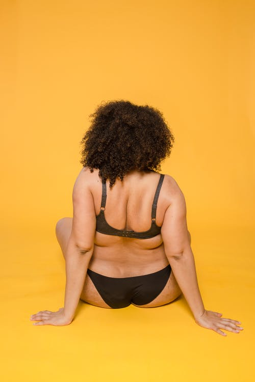 Back view of unrecognizable plus size female in brassiere and panties leaning with hands on yellow surface