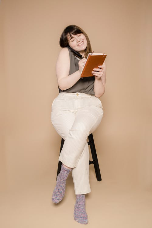 Full body of cheerful young female with closed eyes having phone call and taking notes in notebook against beige background