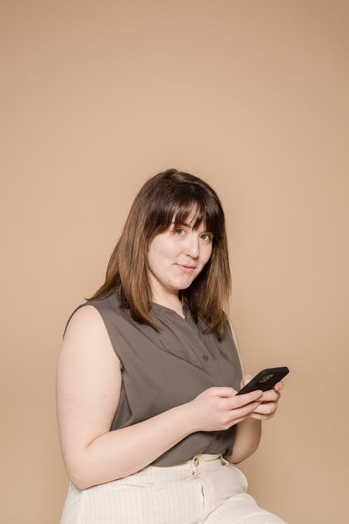 Smiling woman in casual outfit browsing smartphone in studio