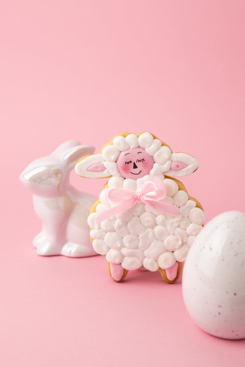 Печенье в форме овцы рядом с яйцом и керамической фигуркой зайчика