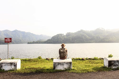 Man Sitting on Gray Concrete Bench Near Body of Water